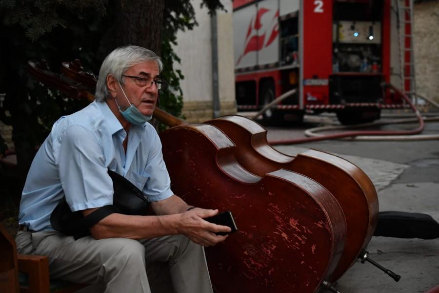 Imaginea neputinței: Dirijorul Petre Neamțu păzind instrumentele salvate de flăcările care au mistuit Filarmonica Națională din Chișinău