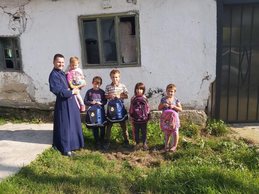 Preotul nu merge doar cu botezul, ci și cu ghiozdanul. Zeci de copii din Groșeni, pregătiți de școală de părintele paroh